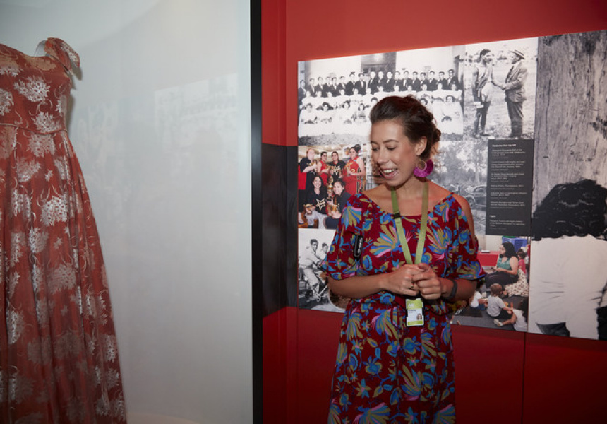 Kimberley Moulton speaking at First People's exhibition, pictured with her grandmother's dress