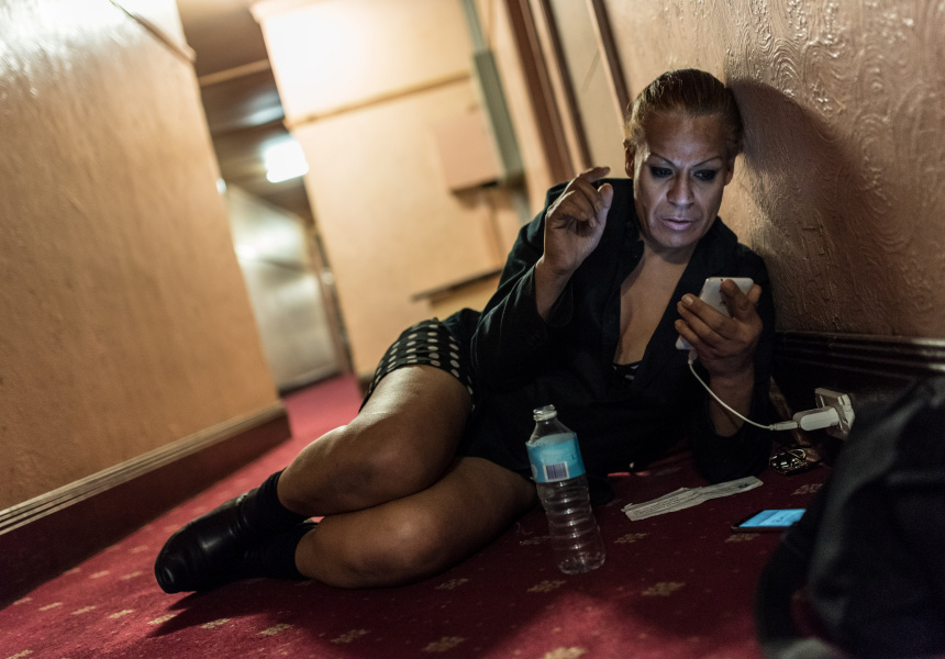 "Charleze, 50, is charging her phone in the hallway. She no longer has a room in the hotel, her ""home sweet home"" for two years. May 2017."