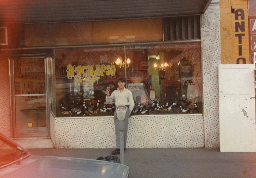 Mario Maccarone in front of the Marios shopfront in 1986, celebrating with a champagne after he received the keys to the shop.