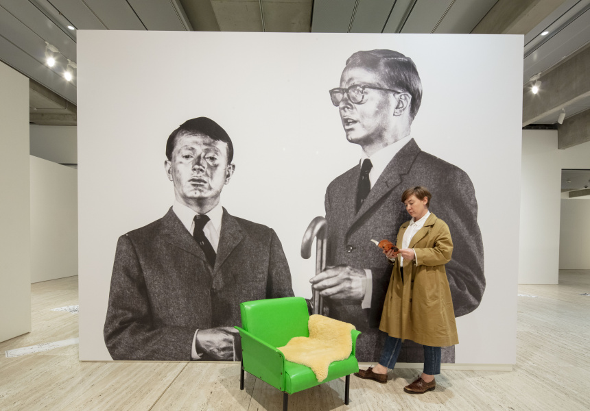 An installation view of Making art public: 50 years of Kaldor Public Art Projects at the Art Gallery of New South Wales, with the box for Kaldor Public Art Project 3: Gilbert & George The Singing Sculpture and Agatha Gothe-Snape's performance work Lion's honey 2019. © Gilbert & George.