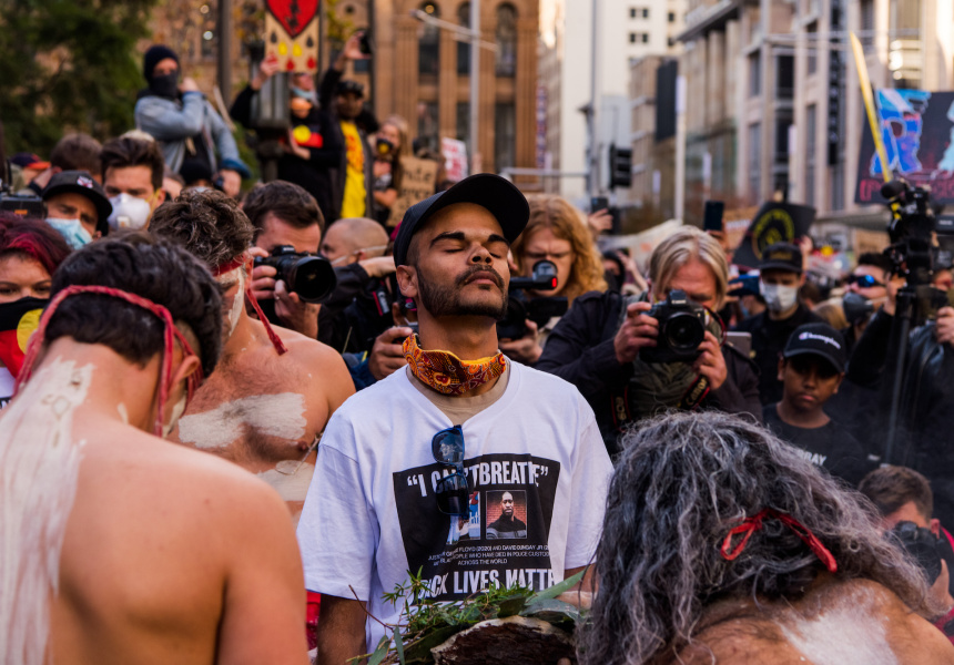 Black Lives Matter protestors pause along with David Dungay's nephew, Paul Silva, near Sydney Town Hall, watched by the media.