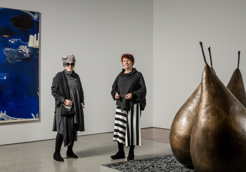 Wendy Whiteley in front of Evening Coming In on Sydney Harbour, 1975, with Tess Baldessin in front of Pear, 1971–72, at Baldessin/Whiteley: Parallel Visions on display at NGV Australia from 31 August 2018 – 28 January 2019. © The Estate of George Baldessin